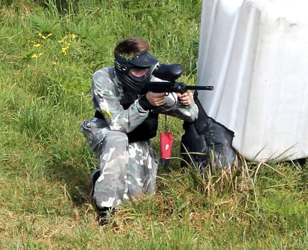 paintball player crouching in grass