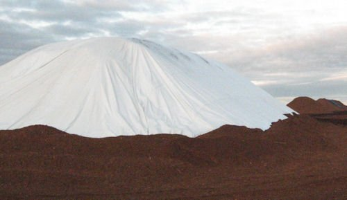 Large stockpile of peat moss covered with 150' x 150' premium grade tarp